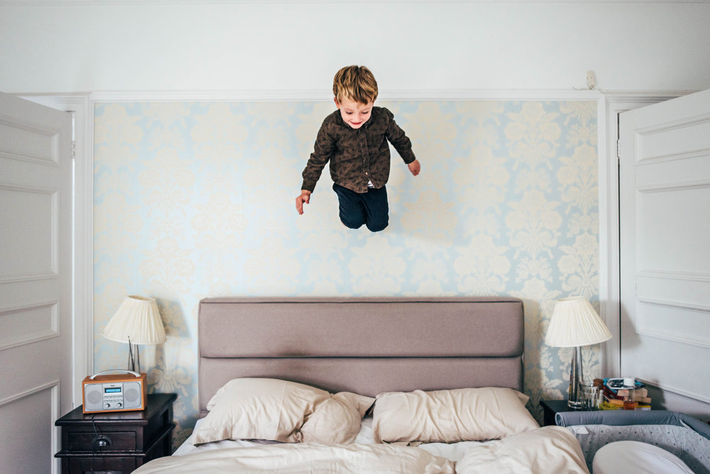 Little Boy mid air jumps on bed At Home Lifestyle Shoot Essex UK Documentary Portrait Photographer