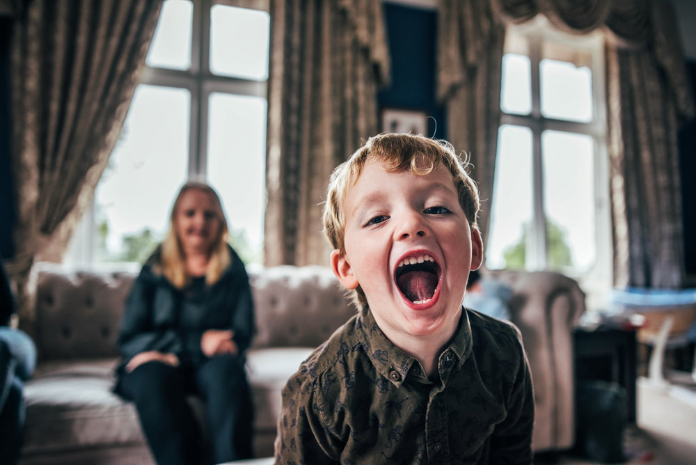 Little boys laugh in camera At Home Lifestyle Shoot Essex UK Documentary Portrait Photographer