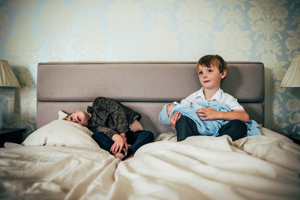 Two boys with new brother on bed At Home Lifestyle Shoot Essex UK documentary Portrait Photographer
