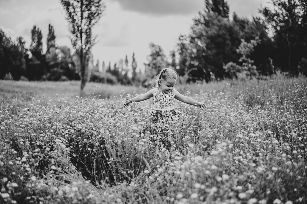 Little girl twirls in Summer Meadow Lifestyle Shoot Essex UK Documentary Portrait Photographer
