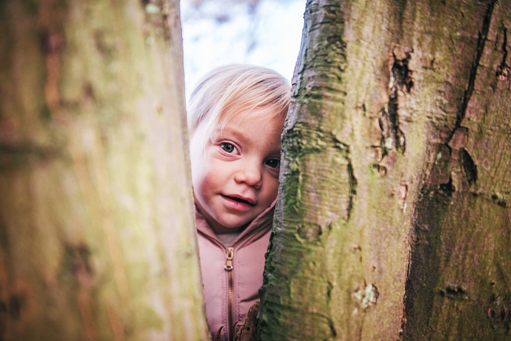 Little girl peeps through tree Lifestyle Shoot Essex UK Documentary Portrait Photographer