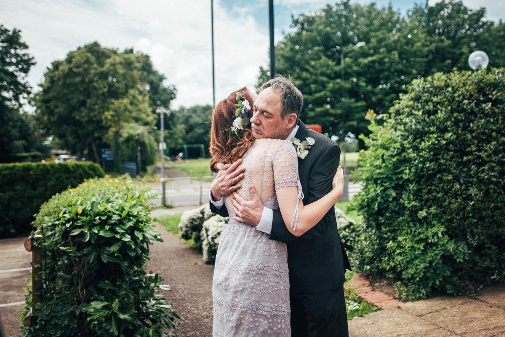Bride vintage Lilac Dress hugs Dad outside Church DIY Hutton Poplars Village Hall Wedding Essex UK Documentary Photographer