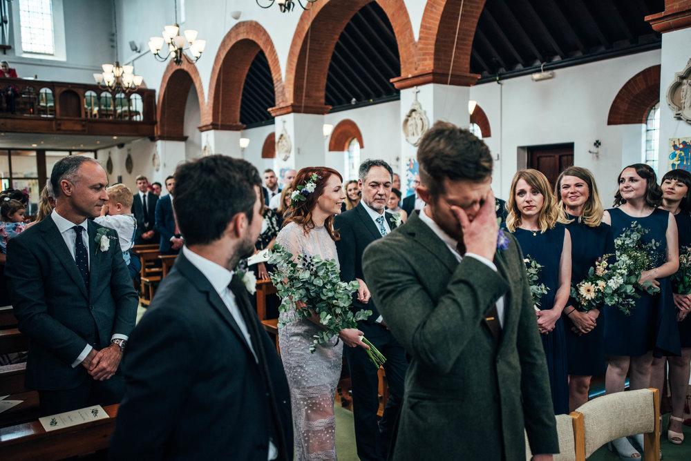 Bride in lilac dress enters church emotional groom for Alternative Brentwood Poplars Village Hall DIY wedding Essex UK Documentary Photographer