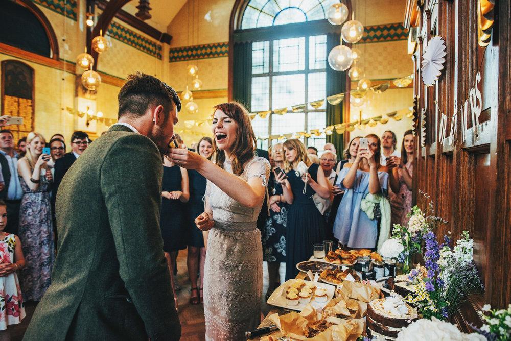 Bride feeds Groom cake vintage lilac dress Hutton Poplars Village Hall DIY Wedding Essex UK Documentary Photographer