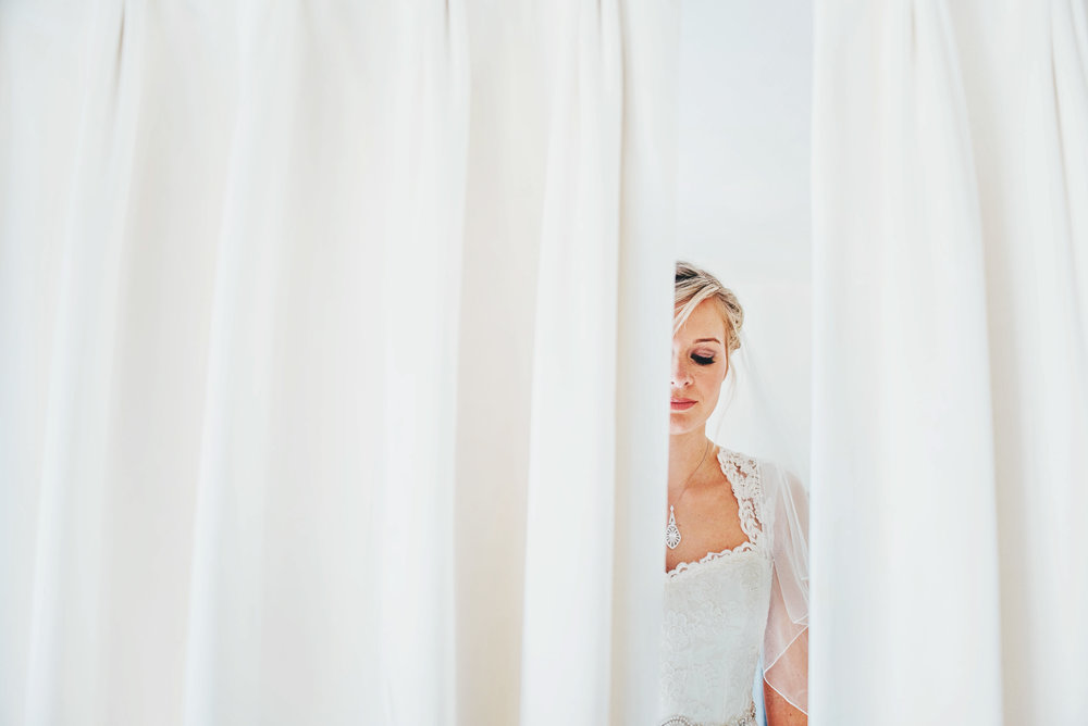 Bride in white curtains at White Heart Great Yeldham Rustic Wedding Essex UK Documentary Photographer