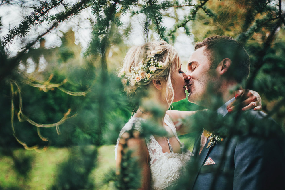 Bride & Groom kiss in trees at White Heart Great Yeldham Rustic Wedding Essex UK Documentary Photographer