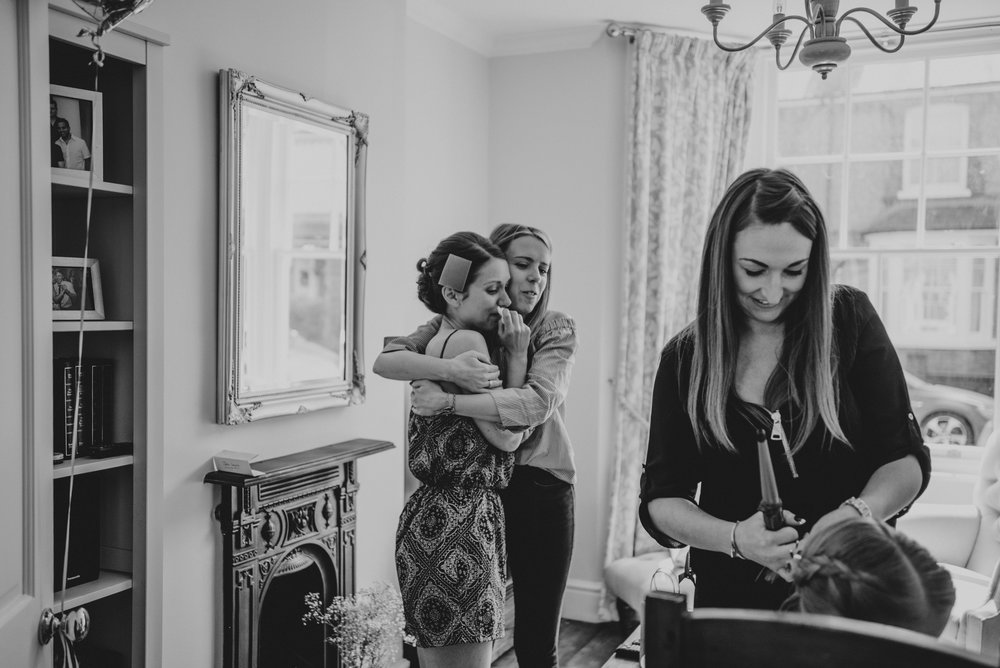 Emotional bride hugs friend during bridal prep for Tipi Stratford Upon Avon Town Hall Wedding Essex UK Documentary Photographer