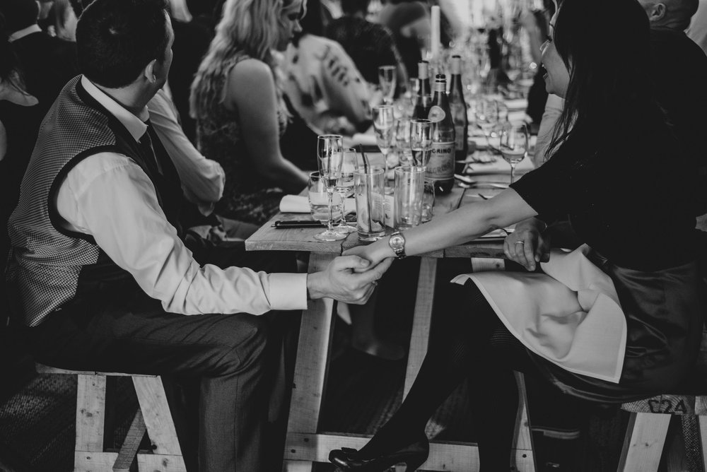 Guests hold hands under table for Stratford Upon Avon Tipi Wedding Essex UK Documentary Photographer