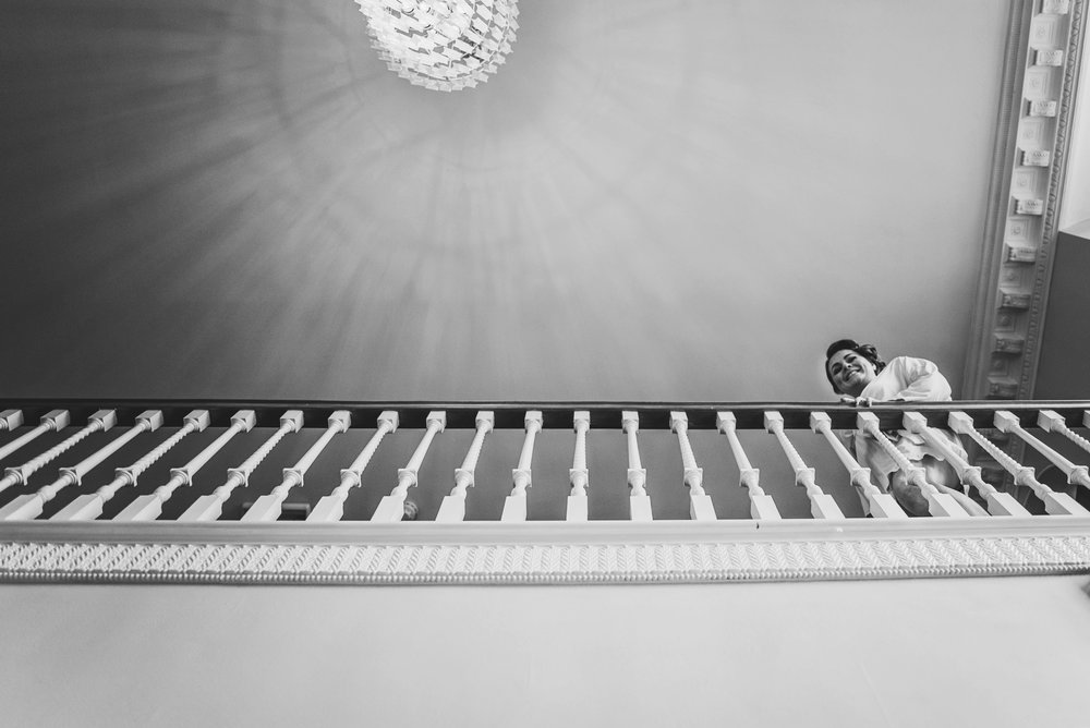 Bridesmaid looks over stairs at Parklands Quendon Hall Essex UK Documentary Wedding Photographer
