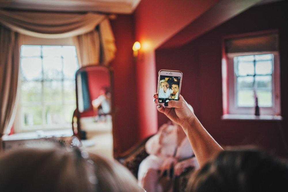 Bride & Bridesmaid take selfie at Parklands Quendon Hall Wedding Essex UK Documentary Photographer