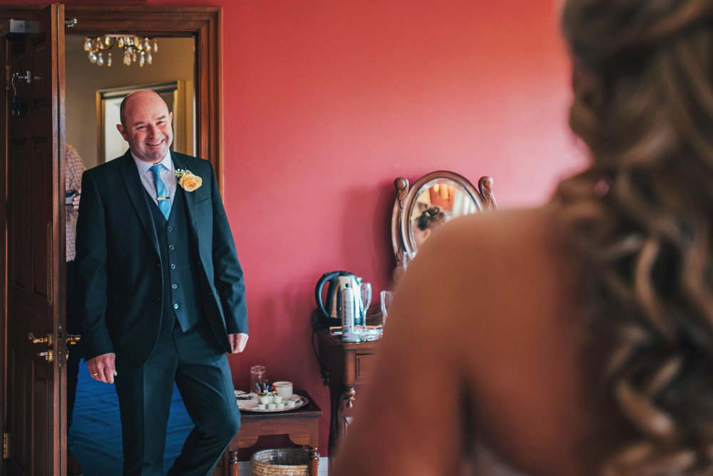 Emotional Father sees his daughter in her wedding dress at Parklands Quendon Hall Essex UK Documentary Photographer