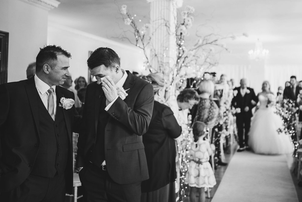 Emotional Groom cries as Bride walks in at Parklands Quendon Hall wedding Essex UK Documentary Photographer