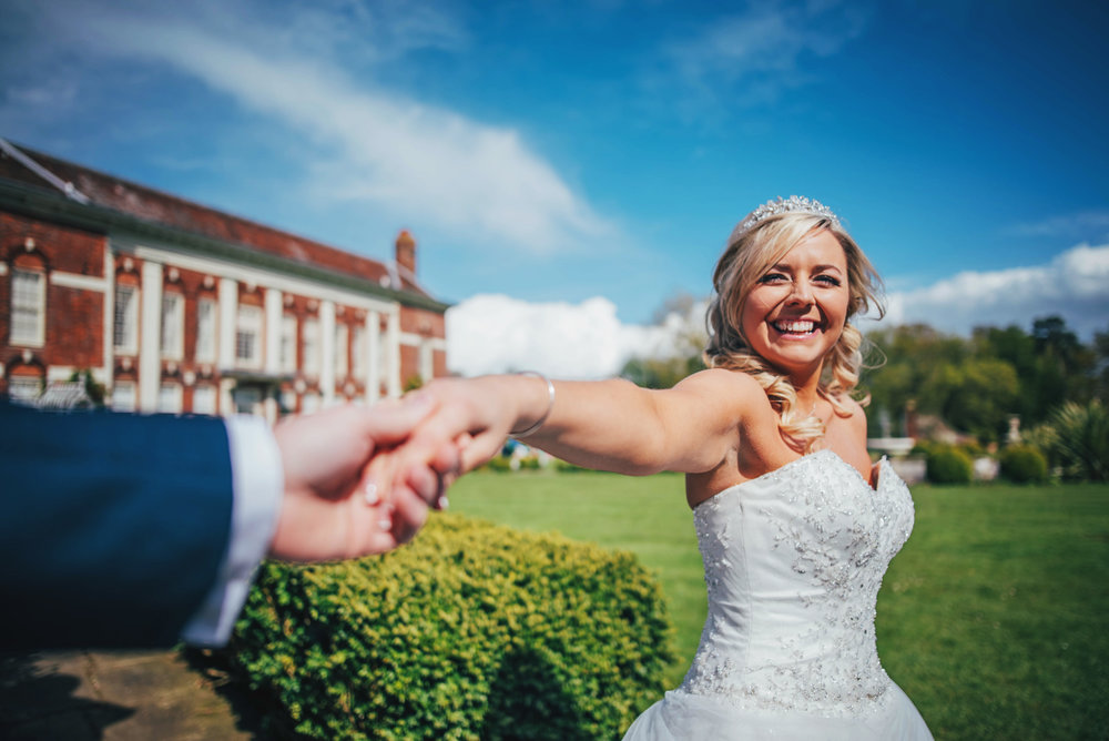 Smiling Bride holds Grooms hand at Parklands Quendon Hall Wedding Essex UK Documentary Photographer
