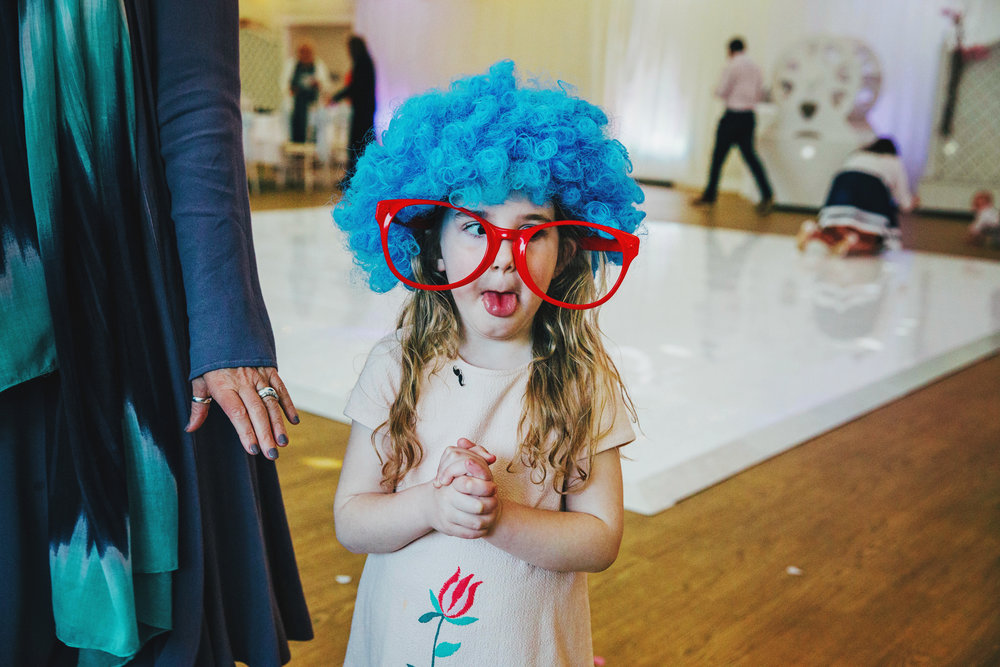Little girl in wig and big glasses on dance floor at Parklands Quendon Hall Wedding Essex UK Documentary Photographer
