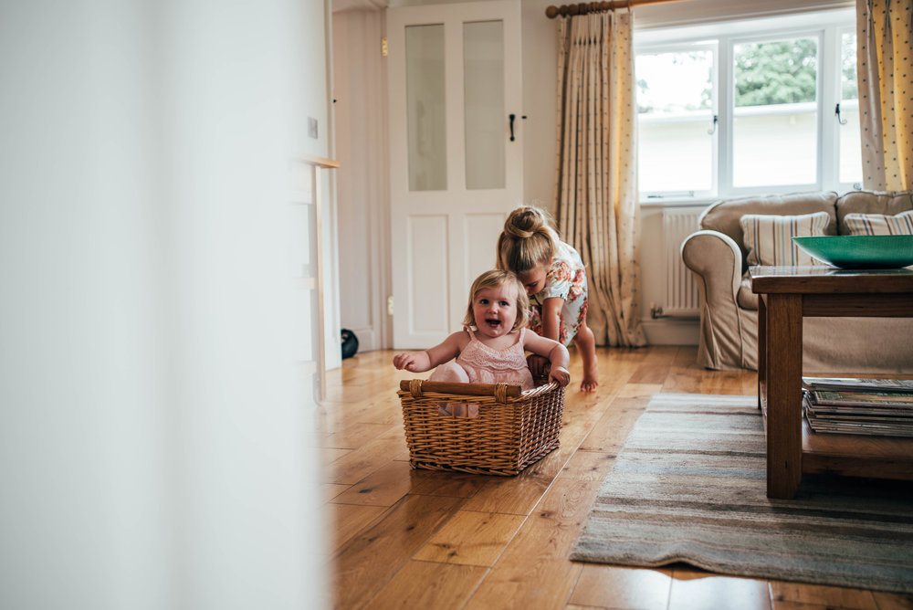 Bridesmaids push baby girl in basket on the floor at Blake Hall Ongar Essex UK Documentary Wedding Photographer