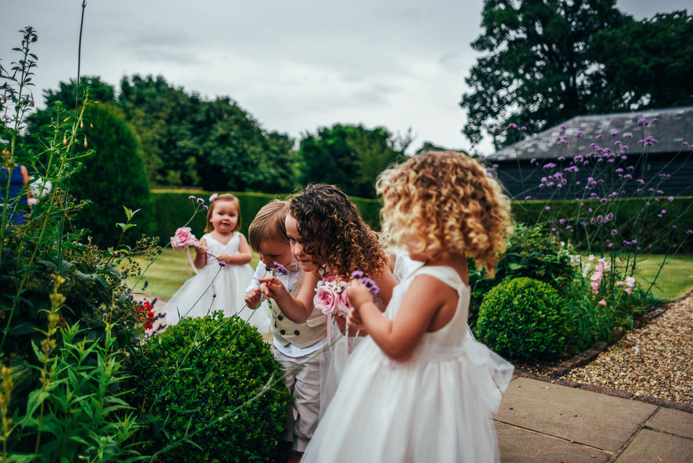 Flower girls smell flowers Blake Hall Ongar Wedding Essex UK Documentary Photographer