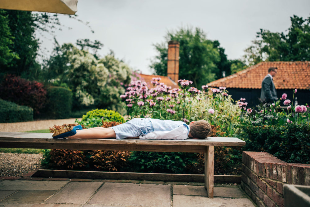 Little boy lays on bench at Blake Hall Ongar Wedding Essex UK Documentary Photographer