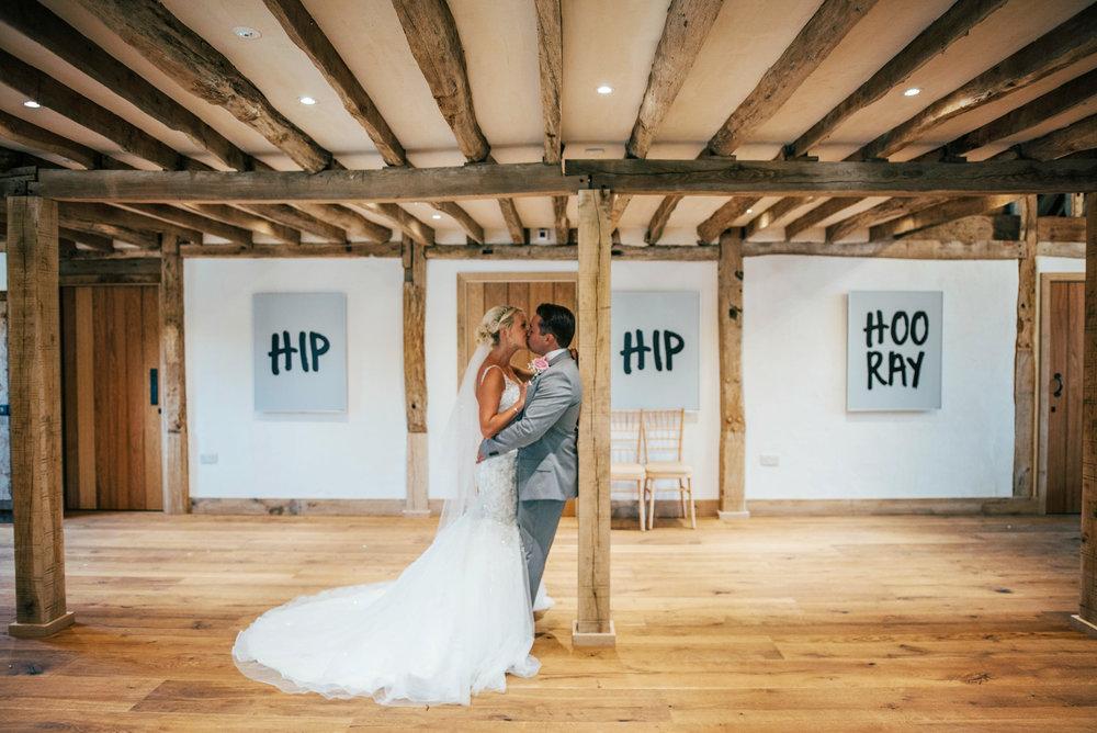 Bride & Groom kiss in Barn Blake Hall Ongar Wedding Essex UK Documentary Photographer