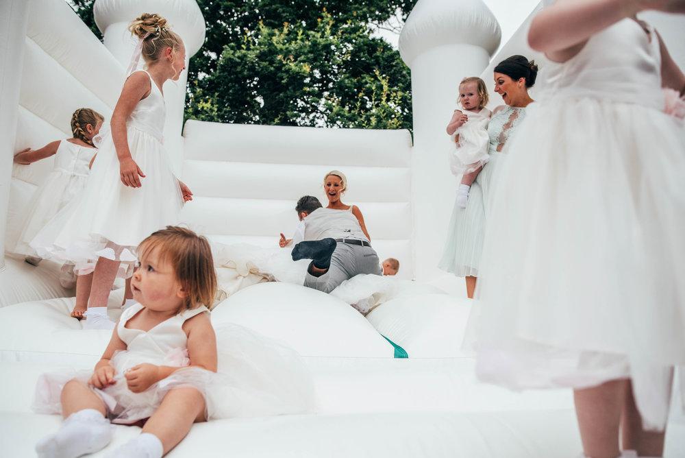 Groom knocks Bride over on Bouncy Castle Blake Hall Ongar Essex UK Documentary Wedding Photographer