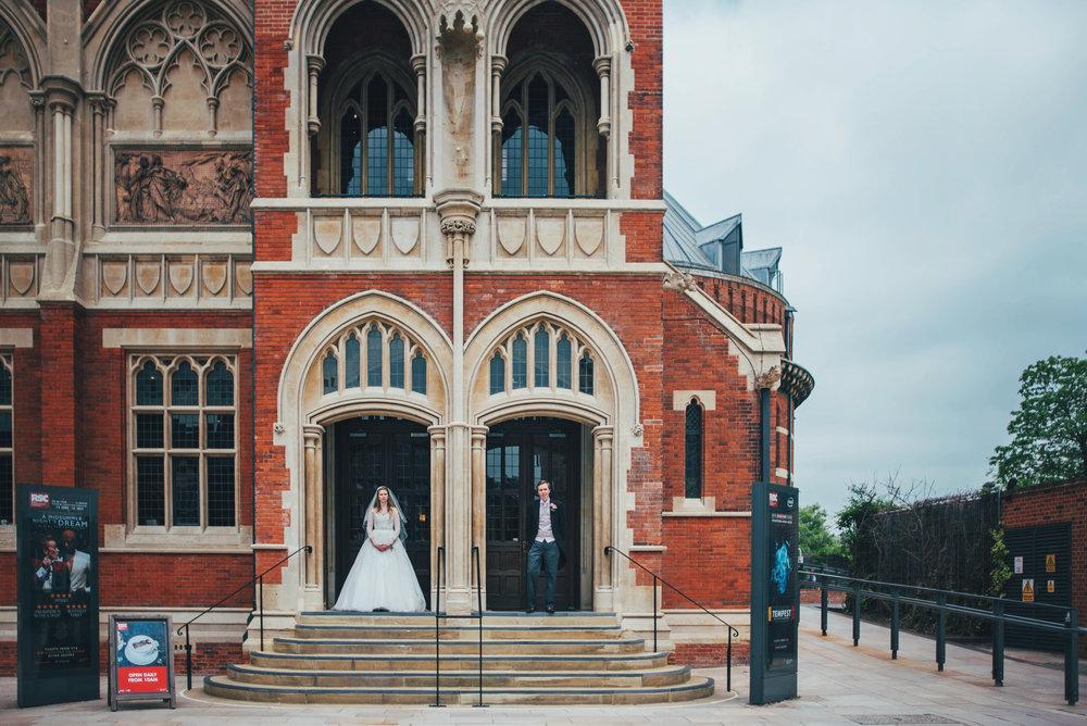 Bride & Groom in doorway of RSC Theatre Stratford Upon Avon Essex UK Documentary Photographer