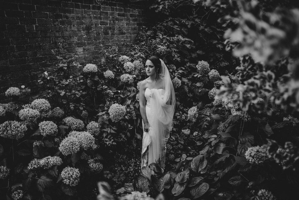 Bride in sunken Magnolia Garden at Dewsall Court Essex UK Documentary Wedding Photographer