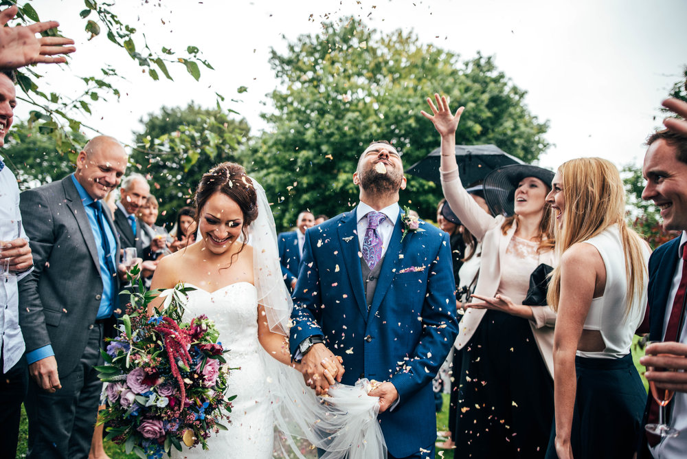 Groom hit in face by confetti at Dewsall Court wedding Essex UK Documentary Photographer
