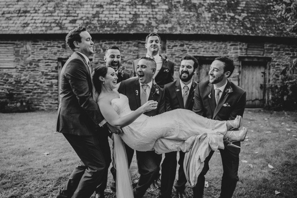 Groomsmen lift Bride at Dewsall Court Wedding Essex UK Documentary Photographer