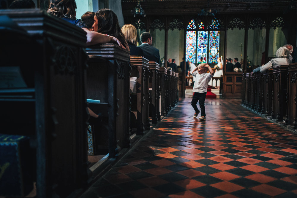 Boy dances in aisle for DIY Farm Wedding Essex UK Documentary Wedding Photographer