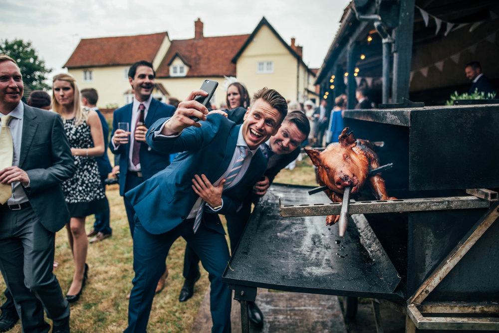 Wedding guests take selfie with Hog Roast for DIY Rustic Farm Wedding Essex UK Documentary Photographer