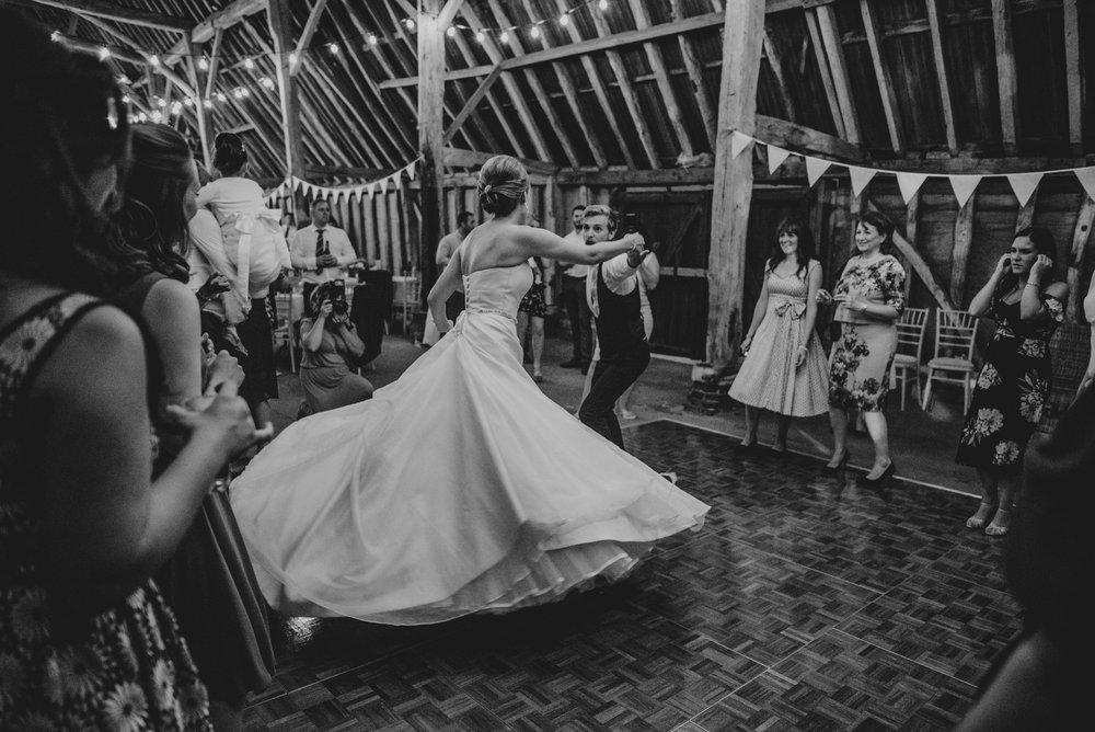 Bride twirls in Pronovias dress on dance floor at DIY Farm Wedding Essex UK Documentary Photographer