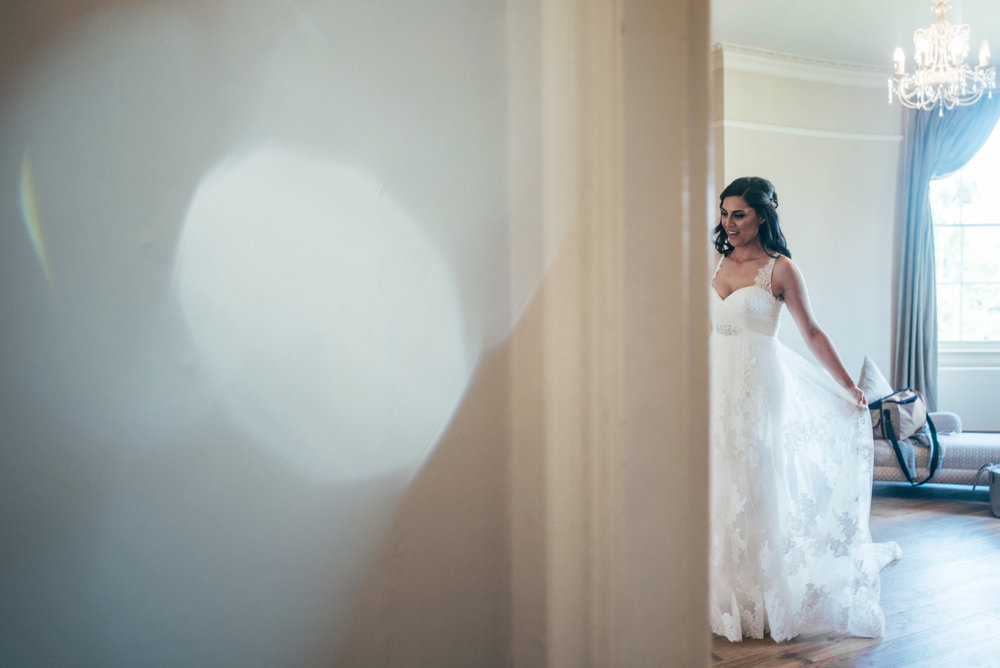 Gorgeous Bride is thrilled with reflection at Hylands House Wedding Essex UK Documentary Photographer