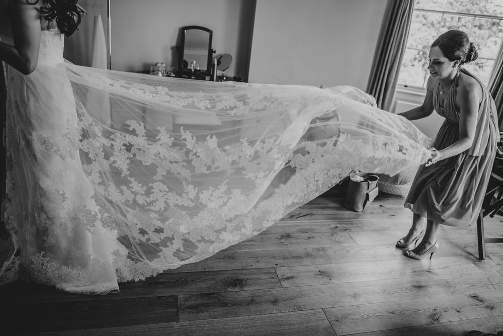 Bridesmaid holds out veil at Hylands House Chelmsford Essex UK Documentary Wedding Photographer
