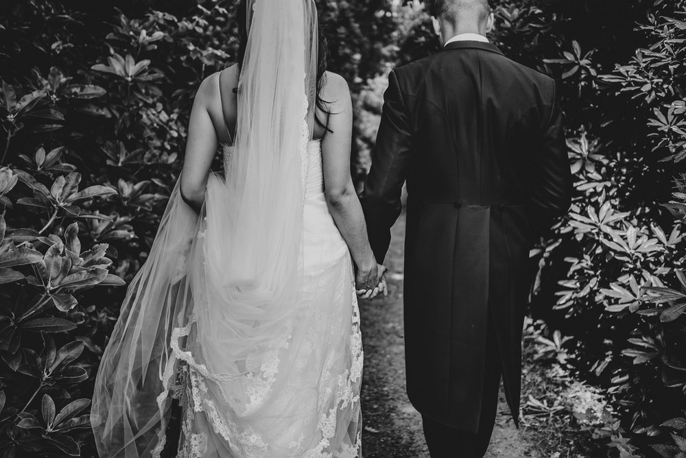Bride and Groom hold hands in gardens of Hylands House Chelmsford Essex UK Documentary Wedding Photographer