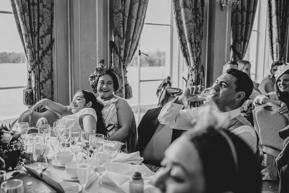 Guests cuddle speeches Hylands House Chelmsford Essex UK Documentary Wedding Photographer
