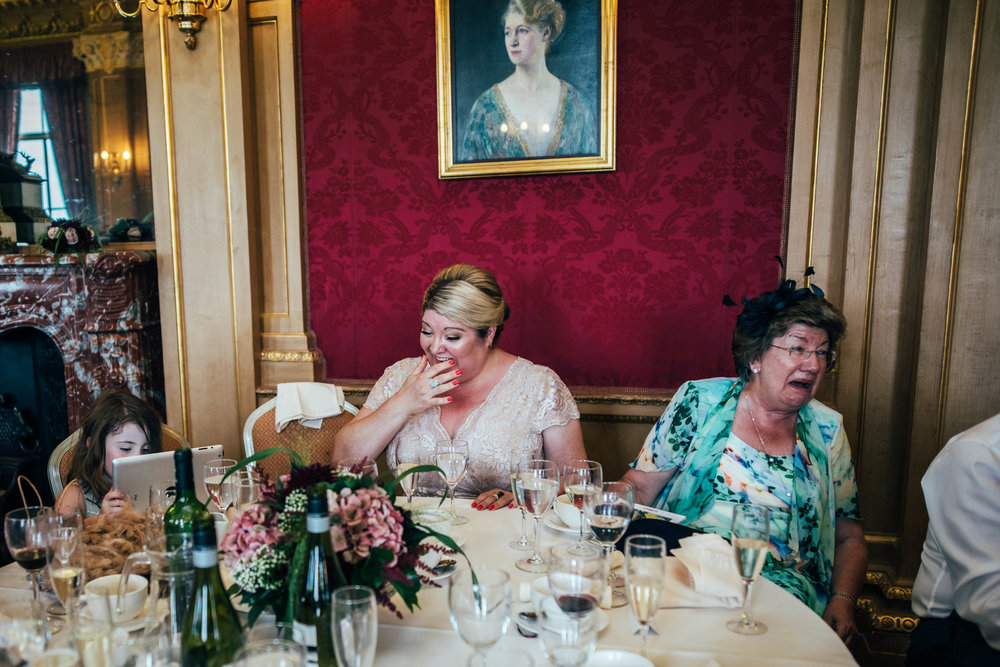 Guests laugh at speeches at Hylands House Chelmsford Essex UK Documentary Wedding Photographer