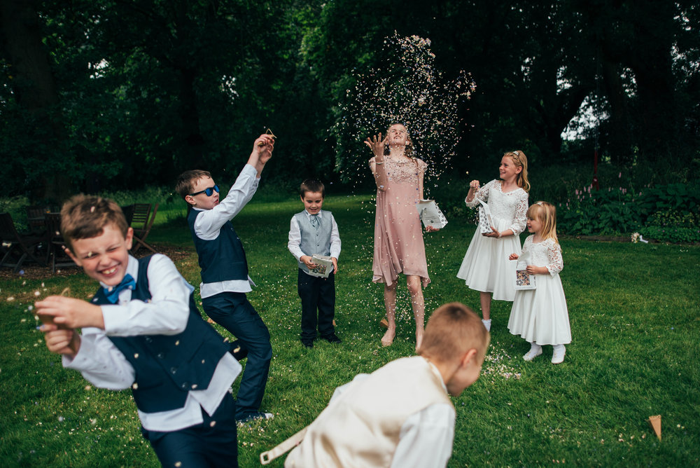 Kids throw confetti at Baddow Park Essex UK Documentary Photographer