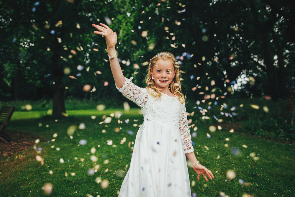 Flower Girl throws confetti at Baddow Park Wedding Essex UK Documentary Photographer