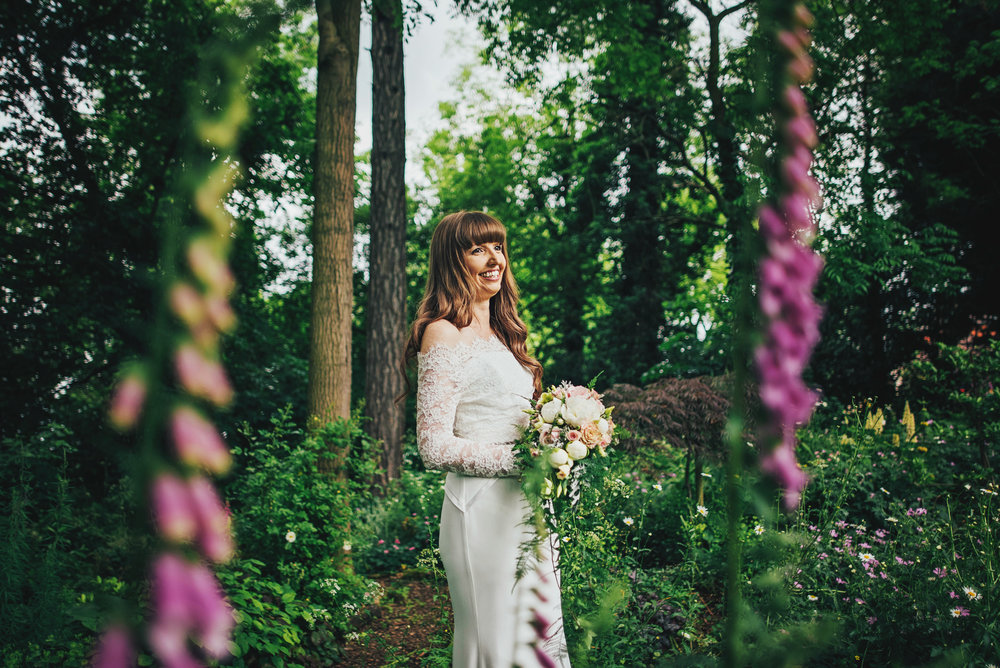 Bride in gardens at Baddow Hall Chelmsford Essex UK Documentary Wedding Photographer