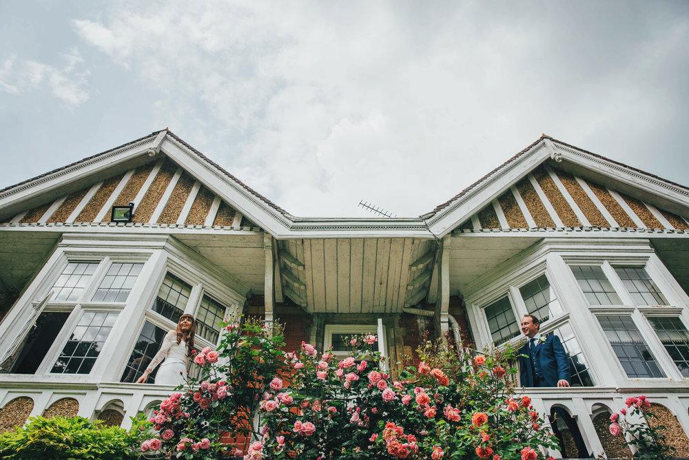 Bride & Groom on balcony at Baddow House Essex UK Wedding Documentary Photographer