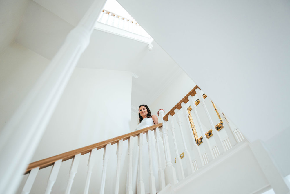 Bride in stairwell for Brentwood Cathedral Blake Hall Ongar Wedding Essex UK Documentary Photographer