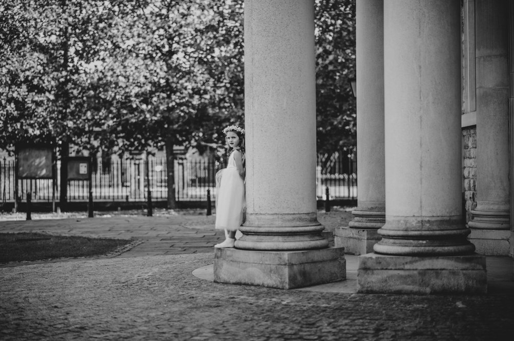 Flower girl waits outside Brentwood Cathedral Essex UK Documentary wedding Photographer