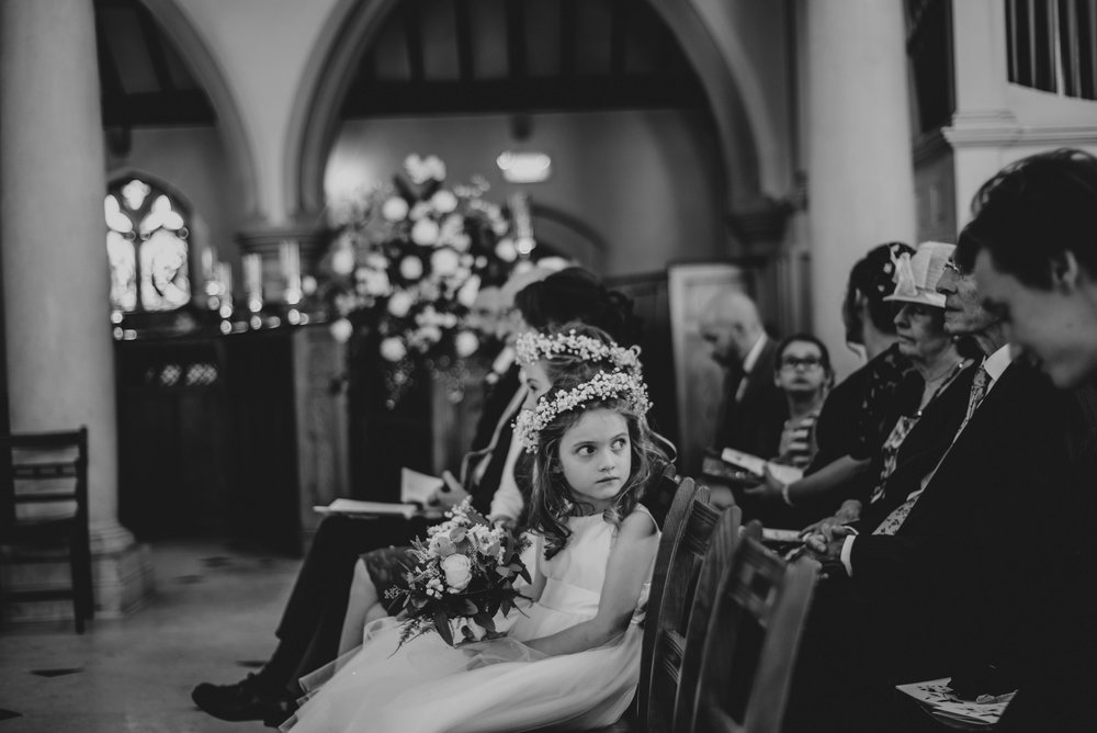 Flower girl is cross with guest at Brentwood Cathedral Blake Hall Ongar Wedding Essex UK Documentary Photographer