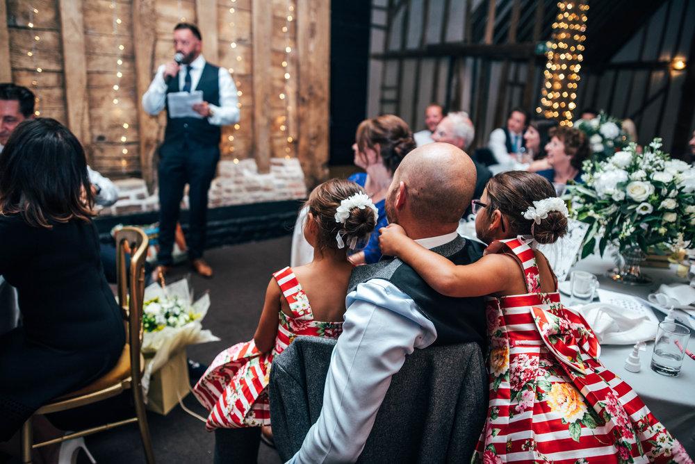Girl cuddles Dad Speeches Blake Hall Ongar Essex UK Documentary Wedding Photographer