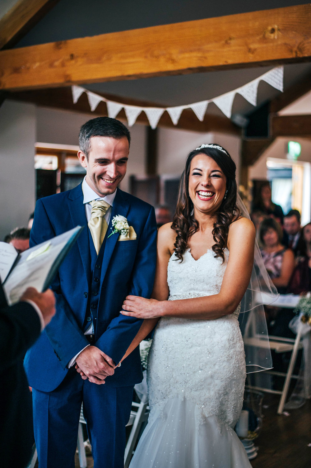Laughing Bride and Groom in ceremony at Maidens Barn Essex UK Documentary Wedding Photographer