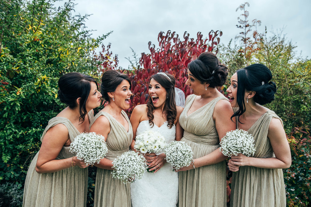 Bride and Bridesmaids laugh for champagne gold Maidens Barn Wedding Essex UK Documentary Photographer