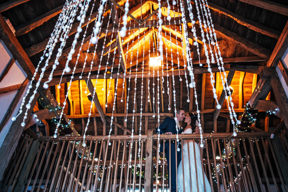 Bride and Groom on balcony under Chandelier at Maidens Barn Chelmsford Essex UK Documentary Wedding Photographer