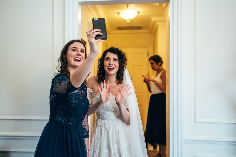 Bride and Bridesmaid take selfie vintage 80s dress gothic diy Rotherwick village hall Essex UK Documentary Wedding Photographer