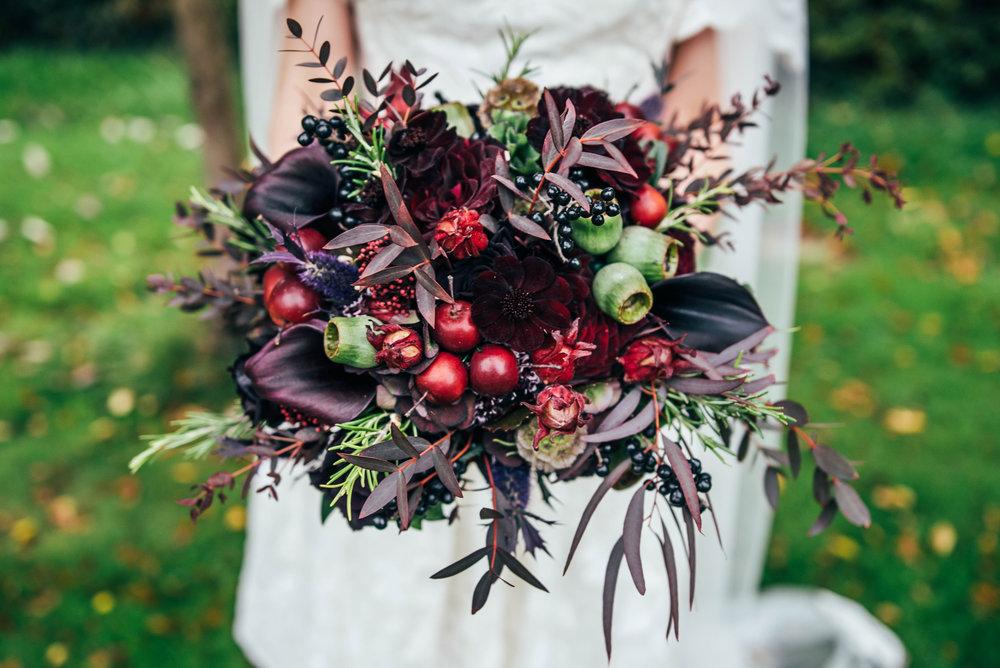 Bride holds Gothic inspired Autumn bouquet DIY Rotherwick Village Hall Wedding Essex UK Documentary Wedding Photographer