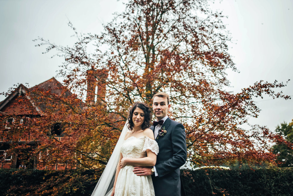 Bride & Groom for Gothic themed Autumn Rotherwick Village Hall wedding Bride wears Vintage 80s dress Essex UK Documentary Photographer