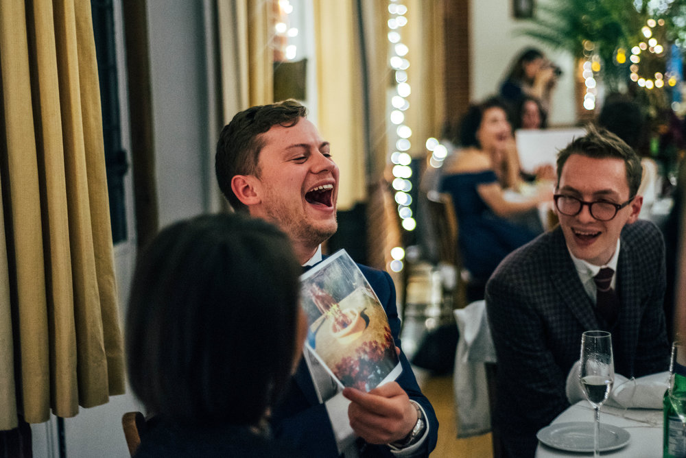 Guest laughing speeches Rotherwick Village Hall gothic diy Essex UK Documentary Wedding Photographer